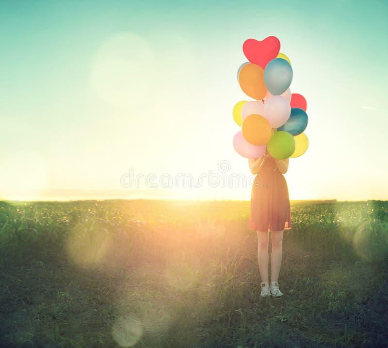 Девочка-подросток красоты на поле лета с красочными воздушными шарами стоковые изображения