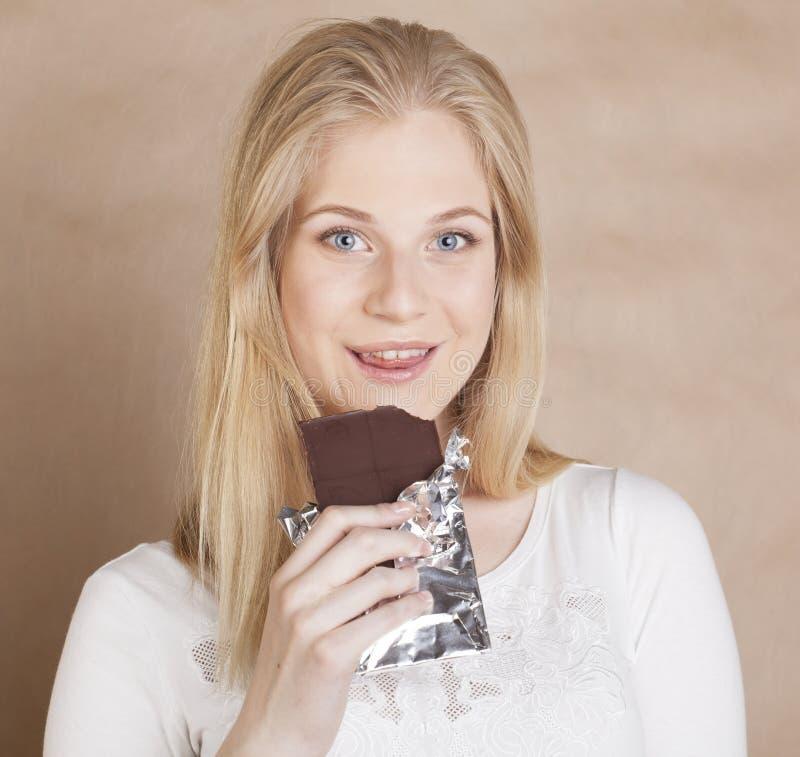Девочка-подросток молодой красоты белокурый есть шоколад стоковые фотографии rf
