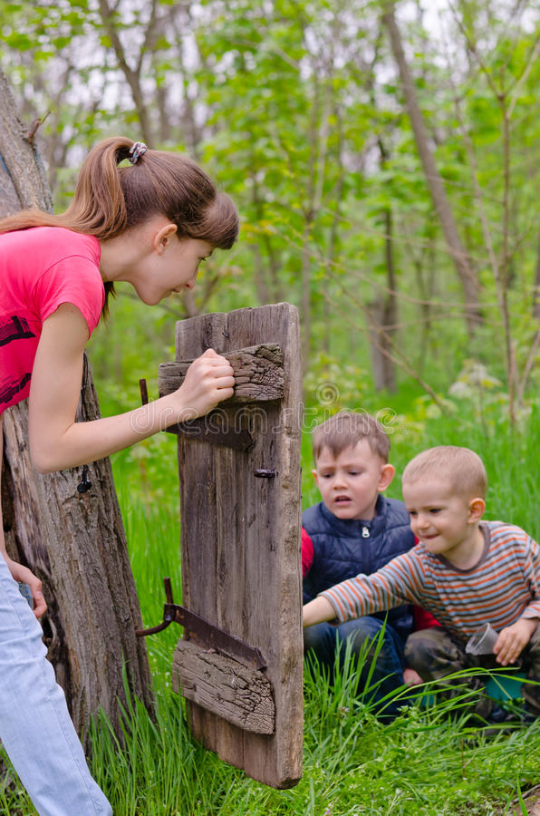 Девочка-подросток наблюдая играть 2 мальчиков стоковые изображения