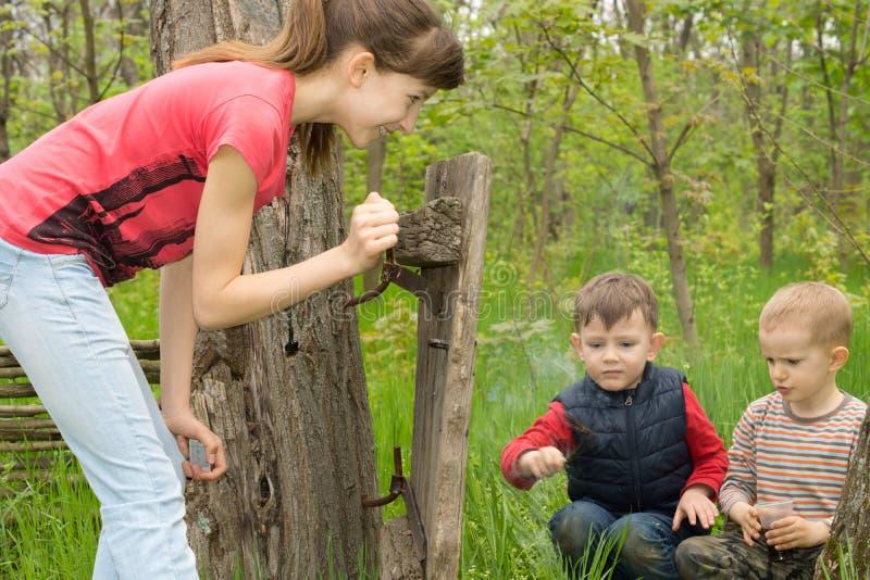 Девочка-подросток наблюдая 2 молодых мальчиков на игре стоковые фото
