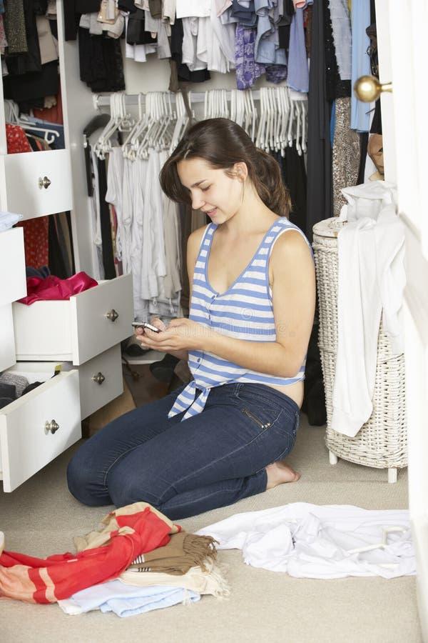 Девочка-подросток на мобильном телефоне окруженном одеждами в шкафе стоковые фото