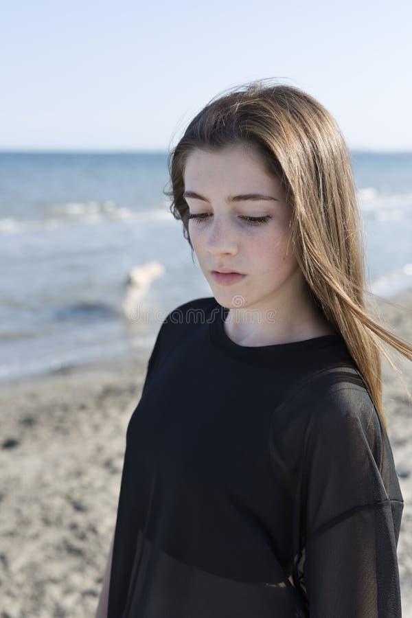 Девочка-подросток представляя на пляже стоковые изображения