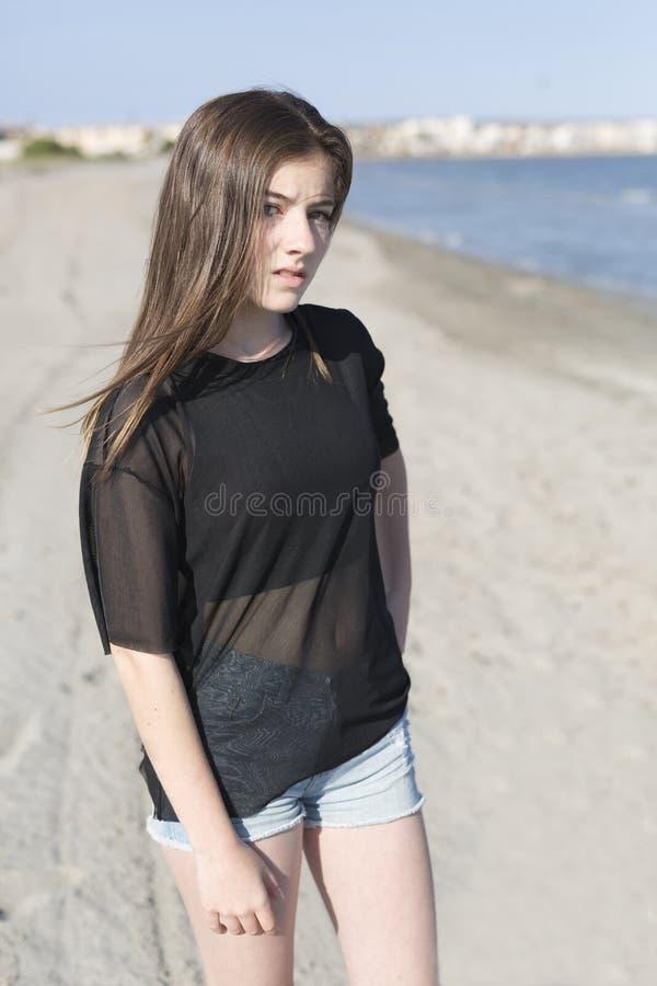 Девочка-подросток представляя на пляже стоковая фотография rf