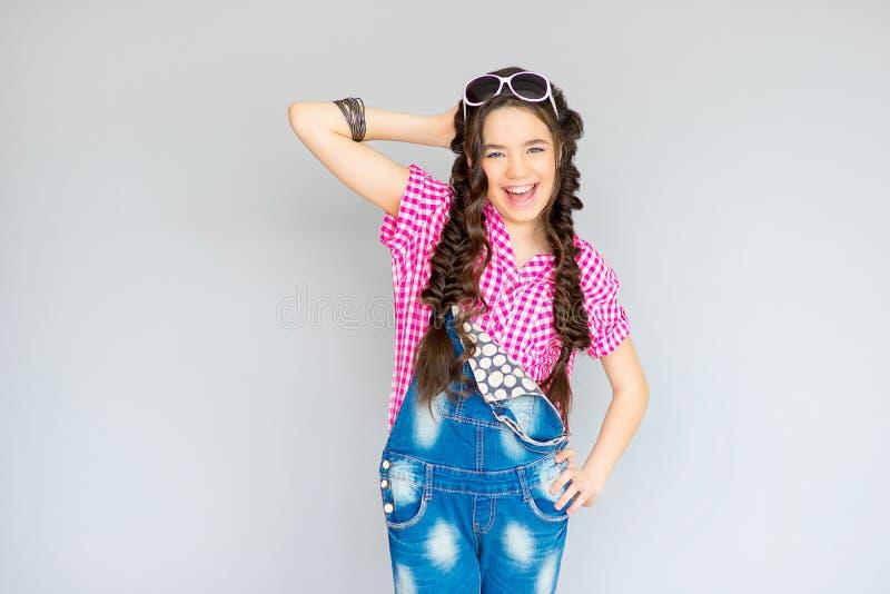 Девочка-подросток представляя на серой предпосылке стоковое фото