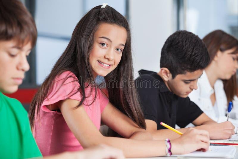 Девочка-подросток сидя при одноклассники изучая на стоковые изображения rf