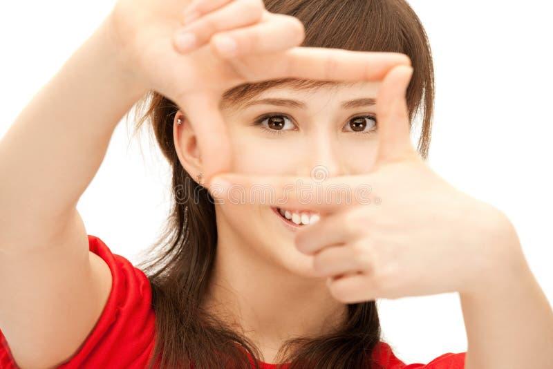 Девочка-подросток создавая рамку с пальцами стоковая фотография