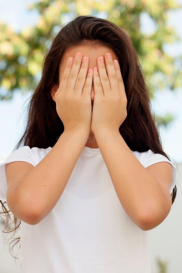 Девочка-подросток с 12 летами старого заволакивания ее сторона стоковое фото