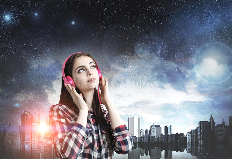 Девочка-подросток с розовыми наушниками, город ночи стоковая фотография