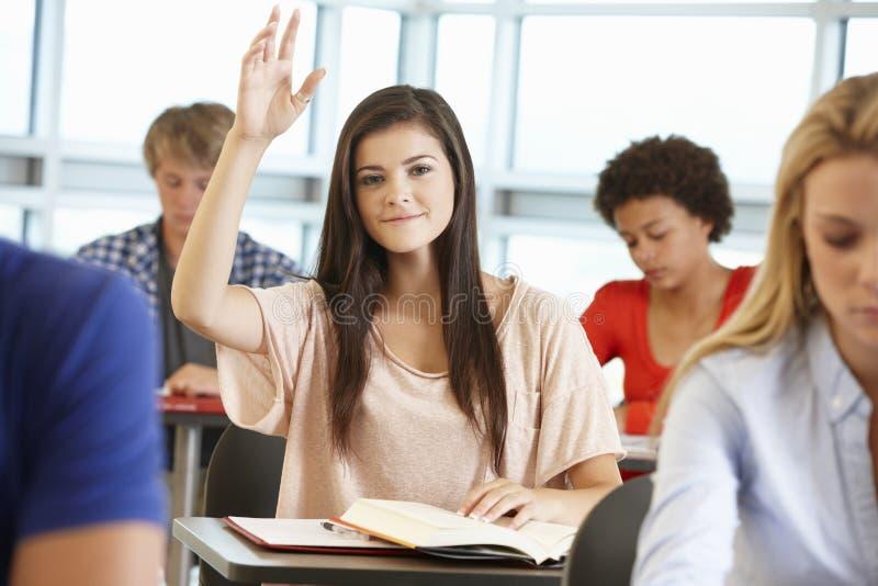 Девочка-подросток с рукой вверх в классе стоковое фото rf