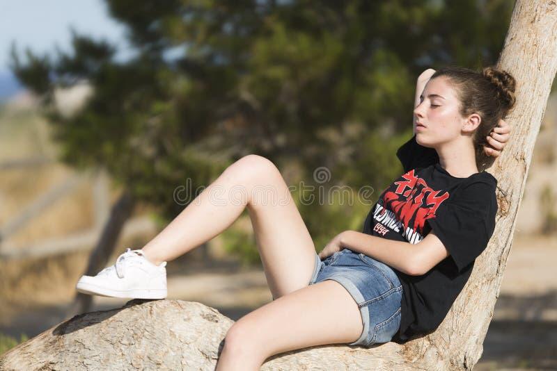 Девочка-подросток уснувший na górze дерева стоковые изображения