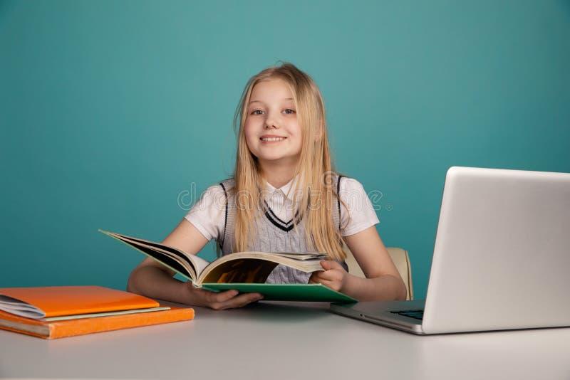 Девочка сидит за столом и читает книгу перед ноутбуком стоковые изображения rf