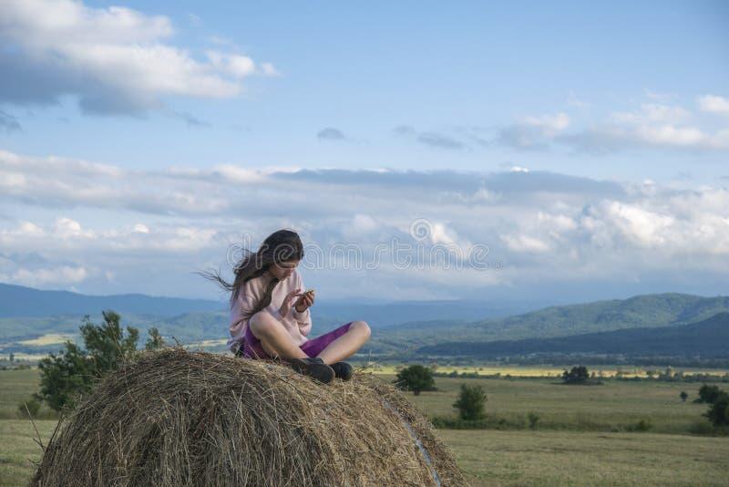 Девочка сидит на стеге сена стоковая фотография