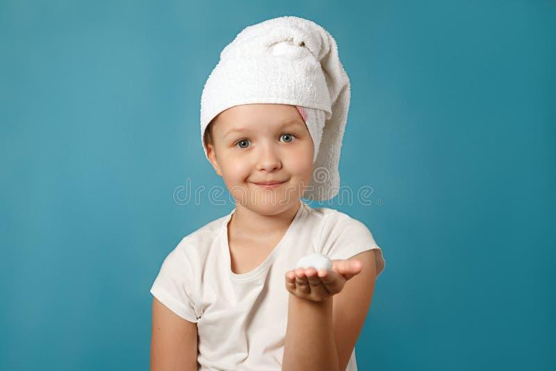 Девочка с белым полотенцем на голове моет лицо на голубом фоне У ребенка на руке пена стоковое изображение rf