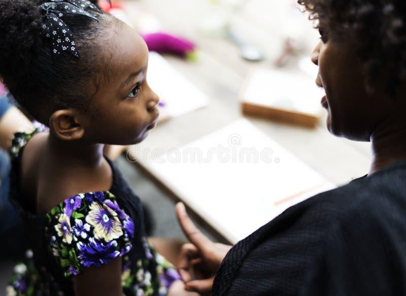 Девушка африканского происхождения слушает к ее учителю стоковые фотографии rf