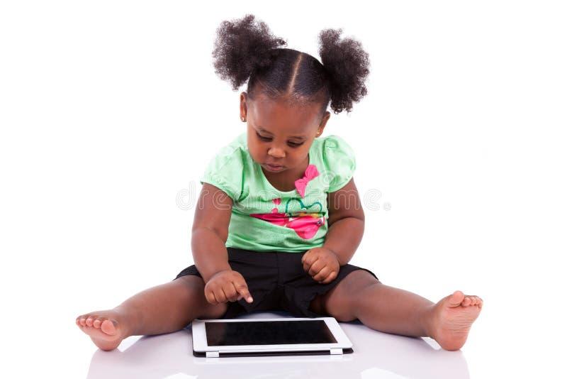 девушка афроамериканца меньшяя таблетка ПК используя стоковое изображение rf