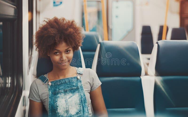 Девушка Афро в выравнивать пустой пригородный поезд стоковая фотография
