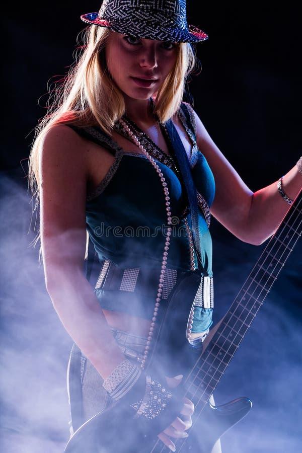 Девушка басовой гитары бросая вызов вы стоковая фотография
