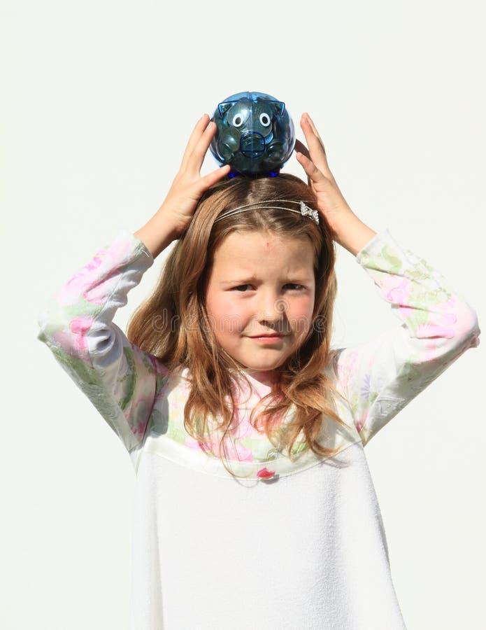 Девушка балансируя с свиньей сбережений вполне денег стоковые фото