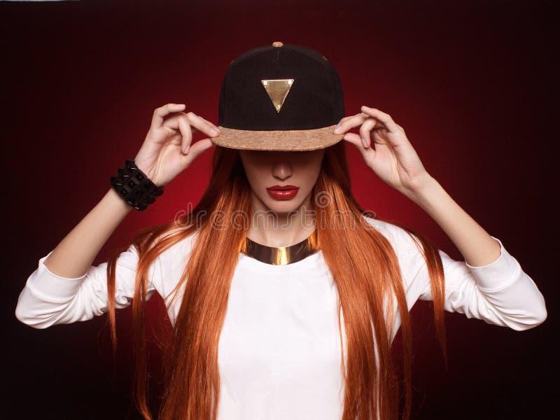 девушка Бедр-хмеля в крышке с длинными красными волосами стоковые фотографии rf