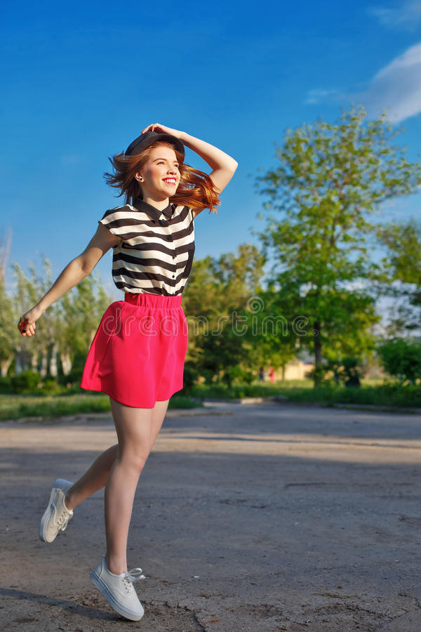 Девушка бежать держащ шляпу стоковое фото