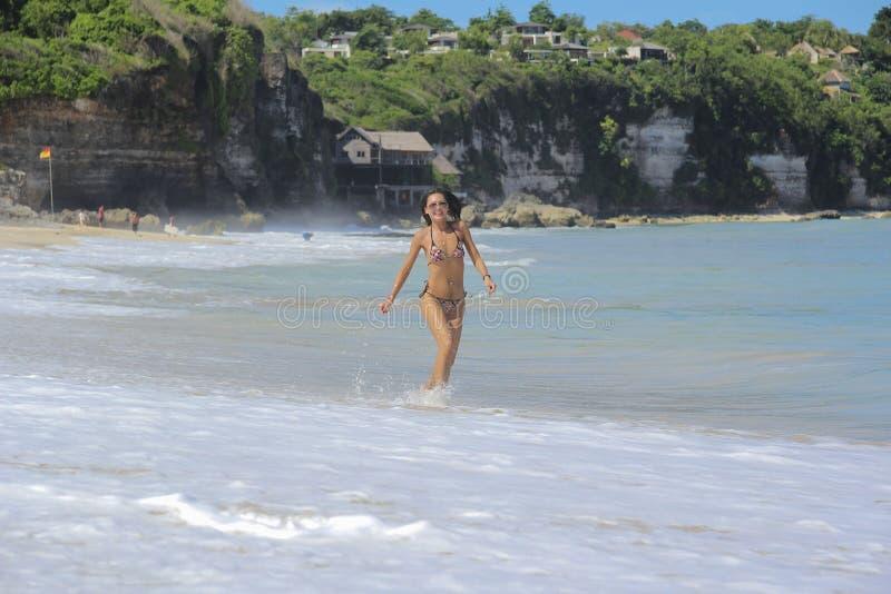 Девушка бежать на волнах вдоль берега океана стоковое фото rf