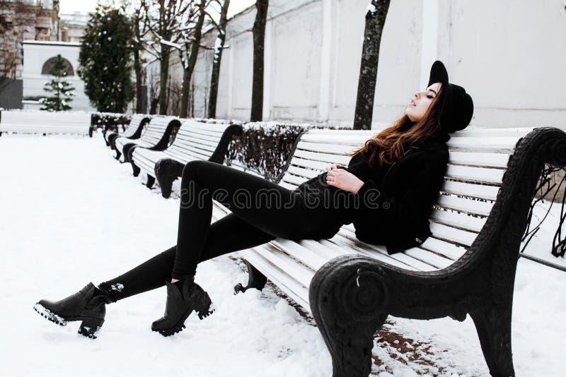 Девушка битника детенышей довольно современная ждать на стенде на парке снега зимы самостоятельно, концепция людей образа жизни стоковая фотография rf