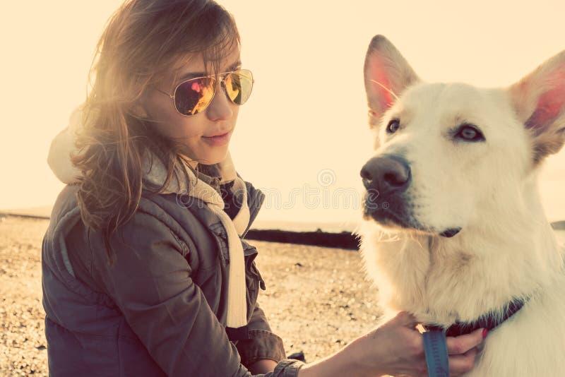 Девушка битника играя с собакой на пляже во время захода солнца, сильном пирофакеле объектива стоковое изображение rf