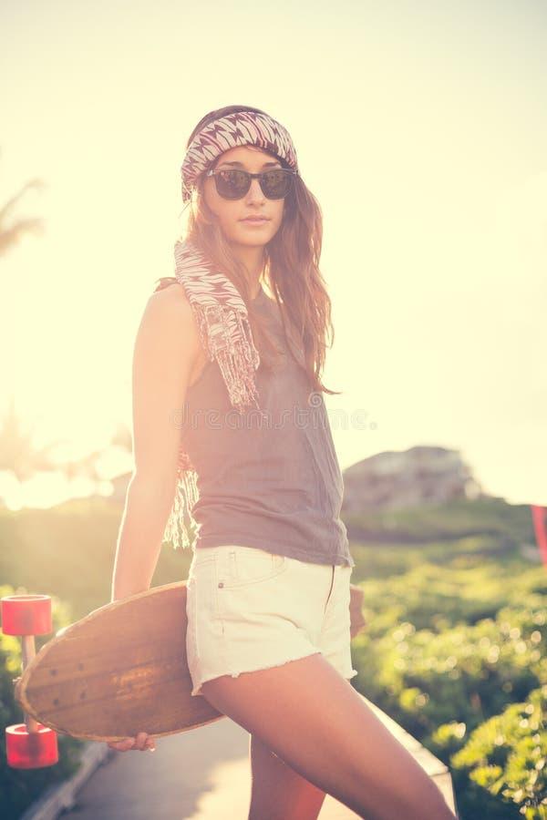 Девушка битника с солнечными очками доски конька нося стоковые изображения