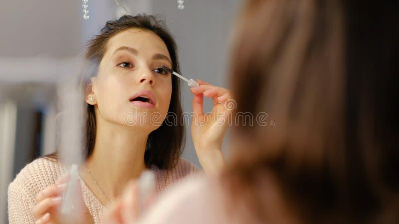 Девушка блога состава красоты консультационная прикладывает тушь стоковая фотография