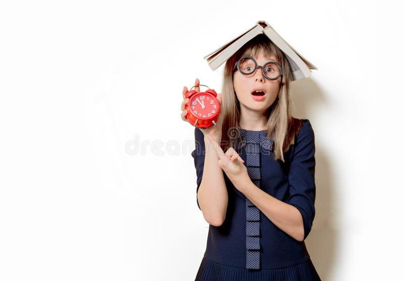Девушка болвана в стеклах с книгами и будильником стоковое изображение