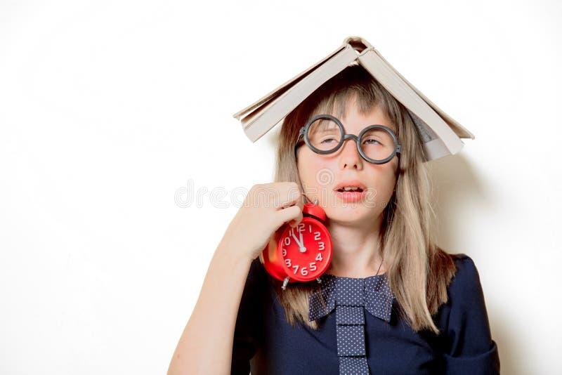 Девушка болвана в стеклах с книгами и будильником стоковое фото
