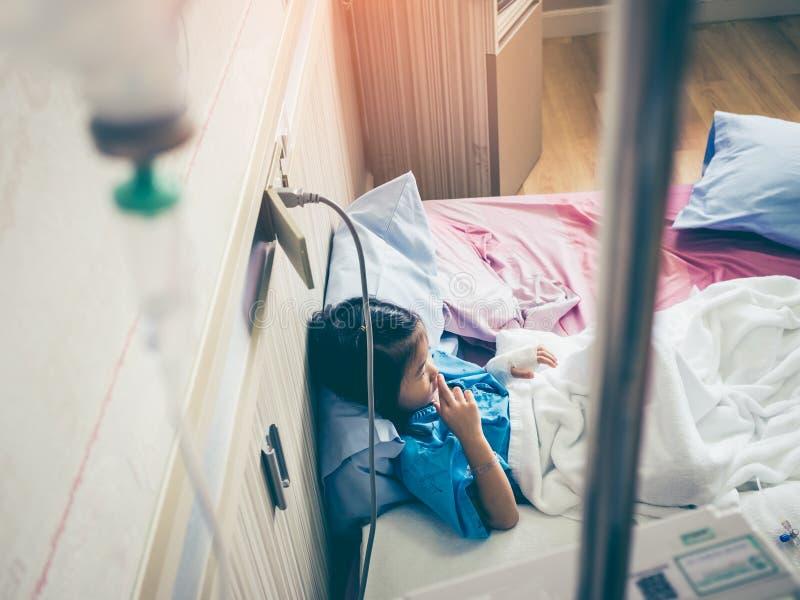 Девушка болезни азиатская сидя на sickbed в больнице с intraveno стоковые изображения