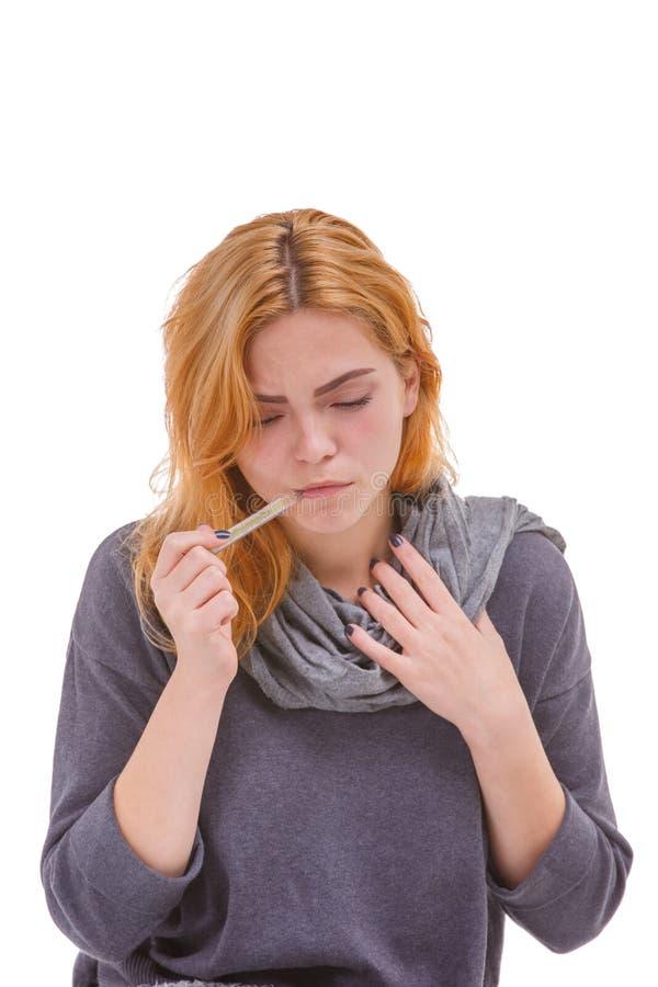 Девушка больного измеряет температуру удар, загоняющий мяч в лунку ` s термометра в ее рот изолировано стоковое изображение rf