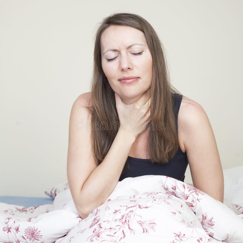 Девушка боли в горле в кровати стоковое изображение rf
