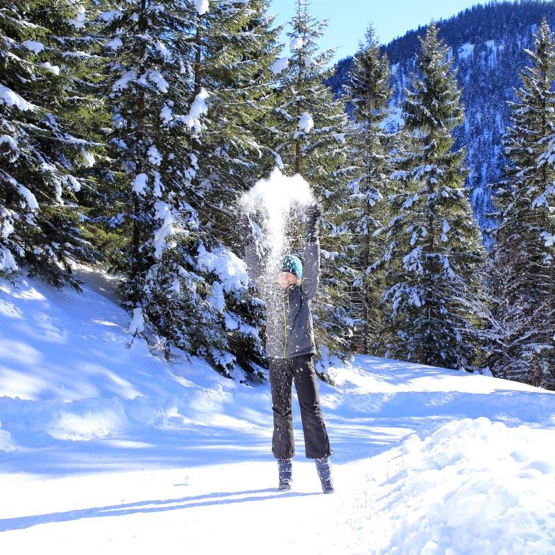 Девушка бросает вверх некоторый снег стоковая фотография