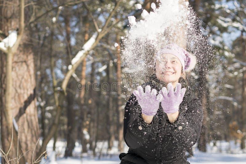 Девушка бросает снег вверх Портрет снега красивой девушки бросая в зиме Счастливая молодая женщина играет с снегом в солнечном wi стоковое фото rf