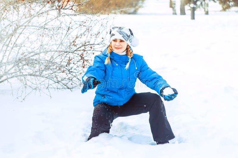 Девушка бросает снежный ком стоковое фото rf