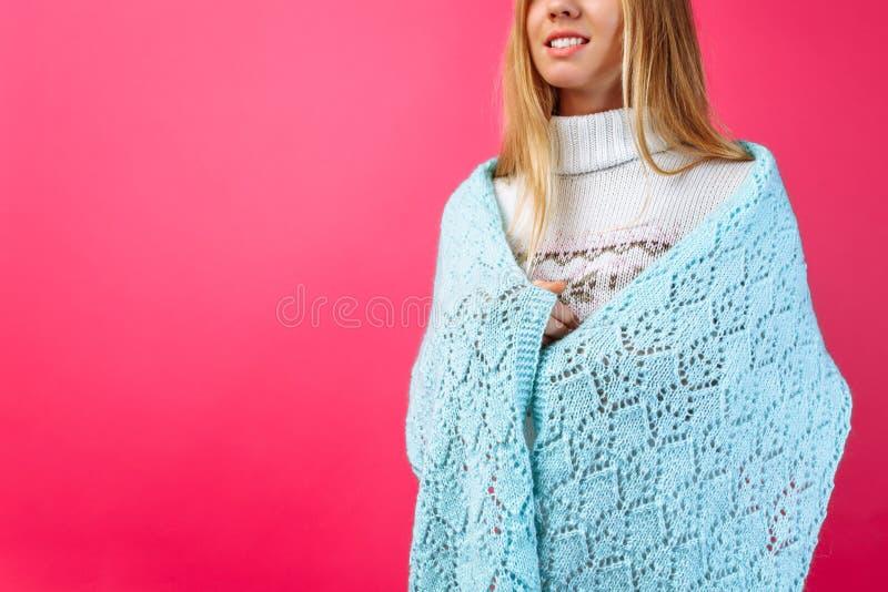 Девушка бросила теплую шаль на ее плечах, на красном backgroun стоковые изображения
