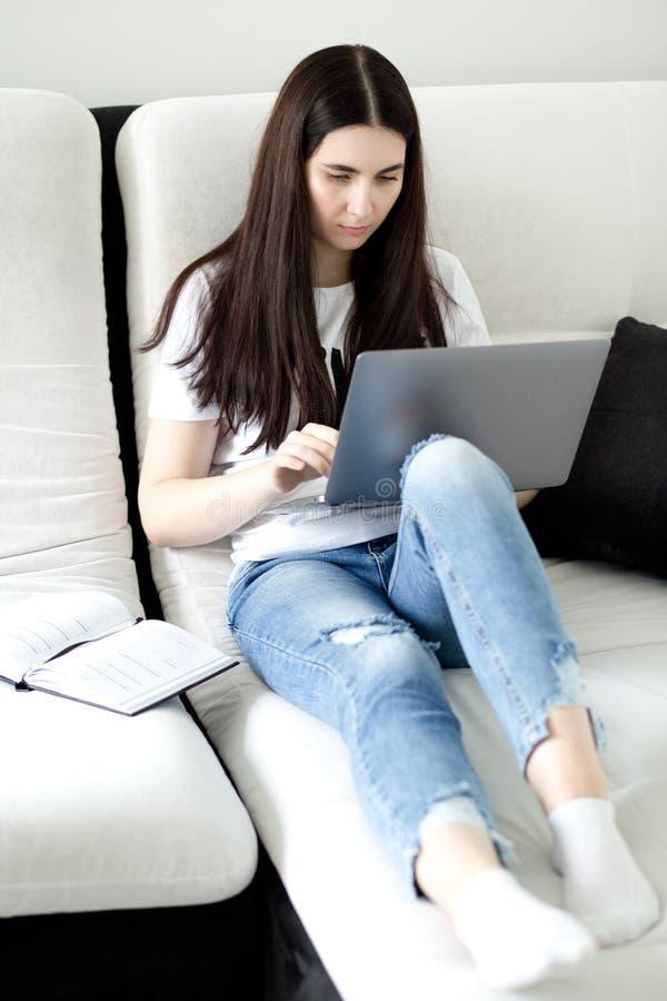 Девушка брюнета используя ноутбук Молодая женщина в случайных одеждах с ее ногами пересекла сидеть на софе r стоковое изображение rf