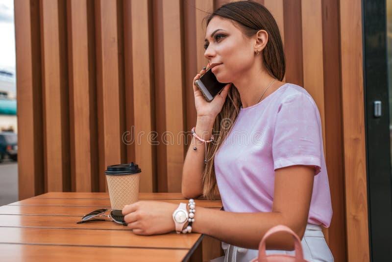 Девушка брюнета сидя в кафе лета Звонки по телефону, на солнечных очках таблицы и чае чашки кофе o стоковое изображение
