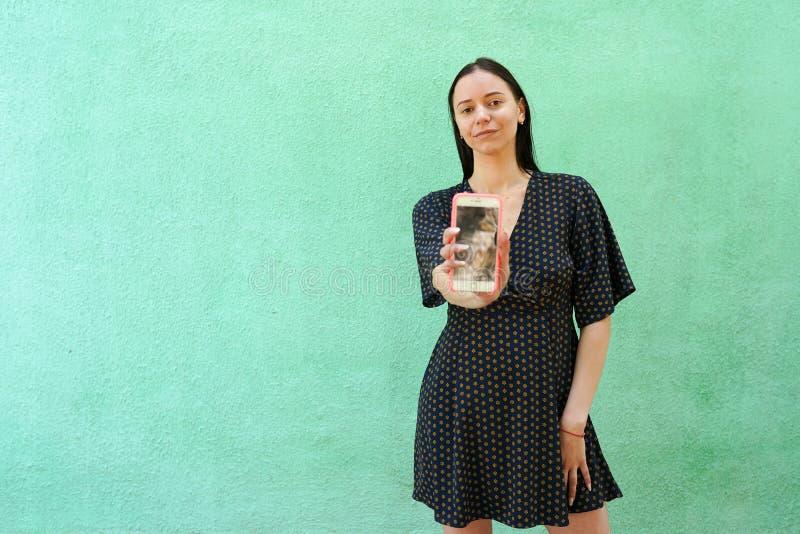 Девушка брюнета со смартфоном на зеленой предпосылке, космосе экземпляра стоковые фотографии rf