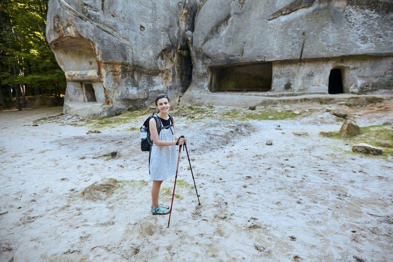 Девушка брюнета стоит около входа к руинам старого города пещеры в утесе стоковое фото
