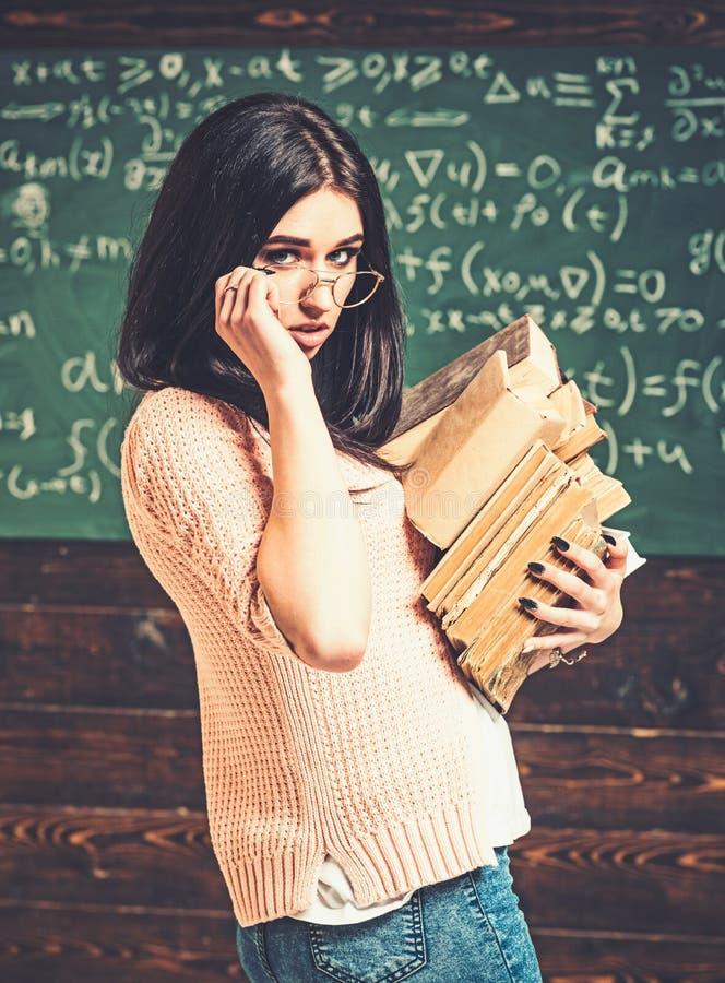Девушка брюнет в розовом кардигане рассматривая ее стекла Куча нося красивой ученицы колледжа взгляда со стороны старых книг стоковые фото