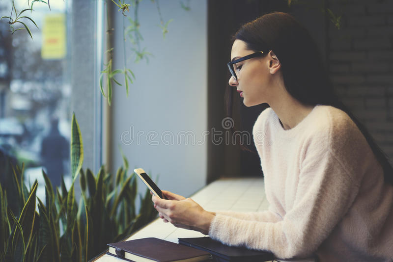 Девушка брюнет в стеклах выполняет болтовню ежедневной работы онлайн при работники контролируя работу компании находясь на праздн стоковое фото rf