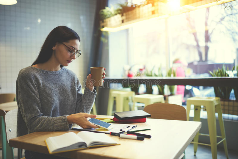 Девушка брюнет в стеклах выполняет ежедневное банковское обслуживание работы через smartphone соединенный к беспроволочному интер стоковые изображения