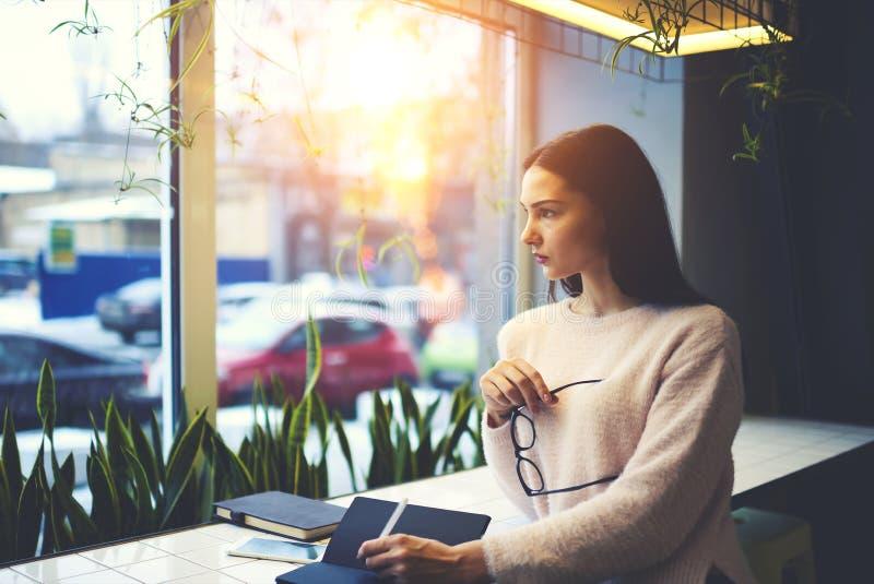 Девушка брюнет в стеклах выполняет ежедневную работу воодушевляя погодой вне окна работая в кофейне стоковое фото