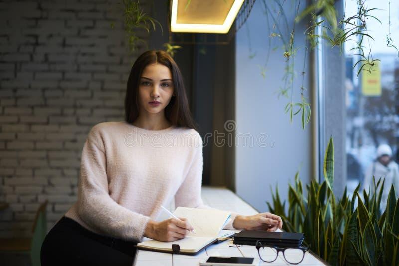 Девушка брюнет в стеклах выполняет ежедневную работу продукции необходимую, что произвело предложение и пожеланные надувательство стоковое изображение rf