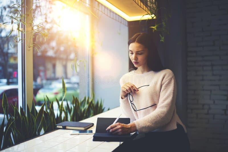 Девушка брюнет в стеклах выполняет ежедневных клиентов работы замечая самые лучшие идеи и решение в личную тетрадь стоковые изображения