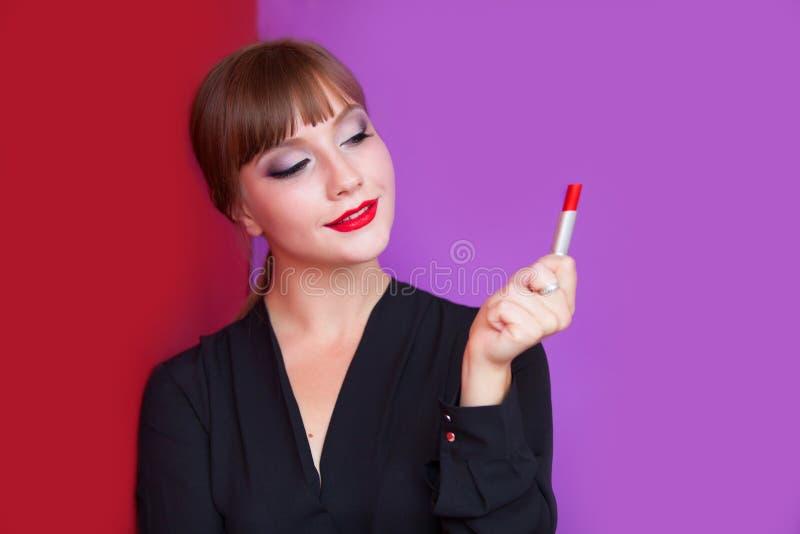Девушка брюнет держа губную помаду стоковая фотография rf