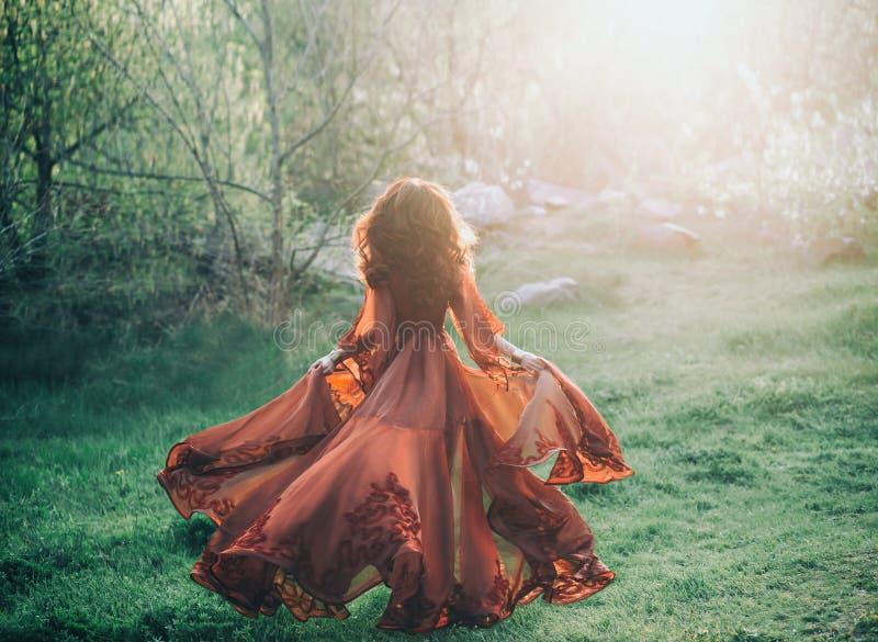 Девушка брюнет с волнистыми, толстыми волосами бежит к встрече солнца Фото от задней части, без стороны Она имеет l стоковое изображение rf